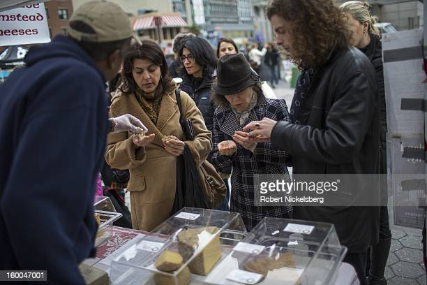 Customers line up at the Cato Corner Farm booth to buy cheese January 12 2013 at the Union Square Farmer's Market in the Manhattan Borough of New...