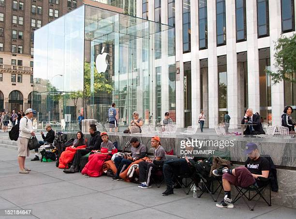 Customers line up outside the Apple store on 5th Avenue awaiting the arrival of the new iphone 5 September 17 2012 in New York Apple said Monday that...