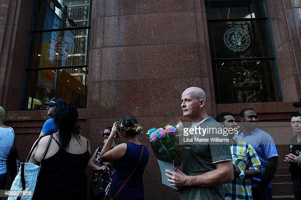 Customers line up outside the Lindt Cafe in Martin Place on March 20 2015 in Sydney Australia The cafe reopened to the public today three months...