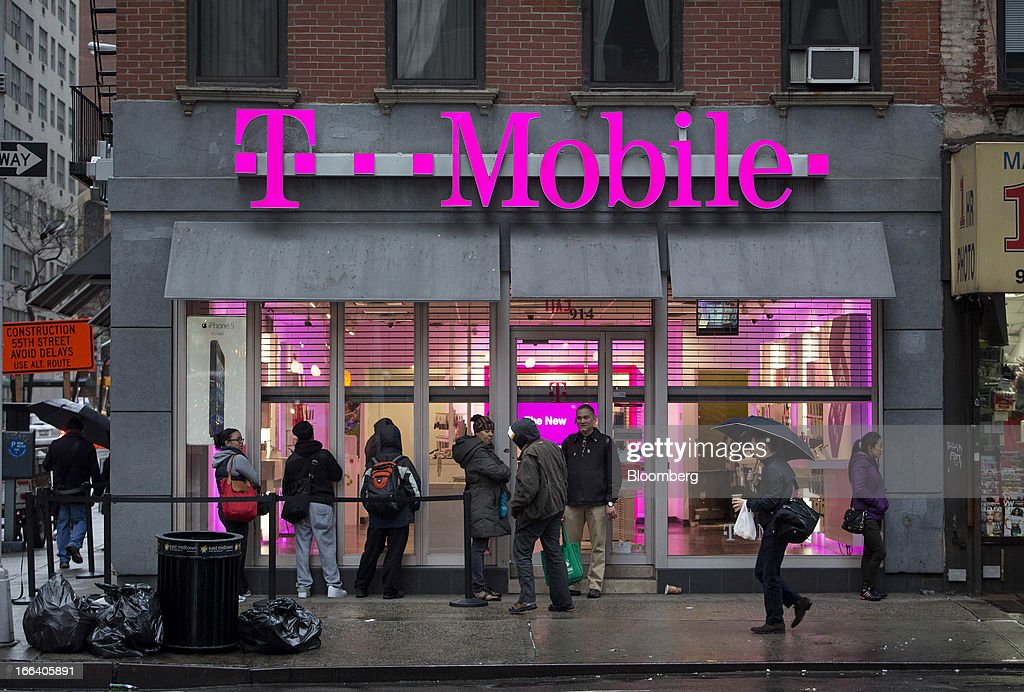 Customers line up to purchase the Apple Inc. iPhone 5 from a T-Mobile USA Inc. retail location in New York, U.S., on Friday, April 12, 2013. T-Mobile USA Inc., the fourth-largest U.S. wireless carrier, will begin offering Apple Inc.'s iPhone for the first time today, providing the biggest showcase yet for its new installment-plan approach to selling phones. Photographer: Scott Eells/Bloomberg via Getty Images