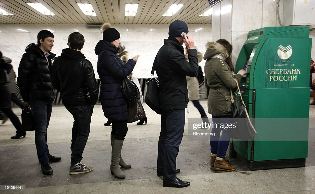 Customers line up to withdraw cash from an automated teller machine (ATM) operated by OAO Sberbank in Moscow, Russia, on Friday, March 22, 2013. Russian lenders with Cypriot units include OAO Sberbank and OAO Gazprombank, both state-controlled, Otkritie Capital, part-owned by VTB, as well as Aton Capital, UralSib Financial Corp. OAO Promsvyazbank and BCS Financial Group. Photographer: Alexander Zemlianichenko Jr/Bloomberg via Getty Images