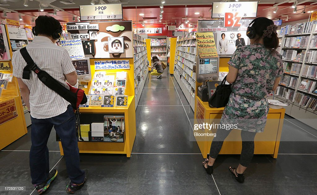 Customers listen to Japanese pop music (J-Pop) at a Tower Records Japan Inc. store in Tokyo, Japan, on Monday, July 1, 2013. Music sales in the country rose for the first time in five years, led by tunes delivered on CDs and other physical media, bucking the trend in developed markets as cheaper downloads gain ground. Physical media made up 82 percent of Japanese music sales last year, versus 37 percent in the U.S., said the Recording Industry Association of Japan. Photographer: Yuriko Nakao/Bloomberg via Getty Images