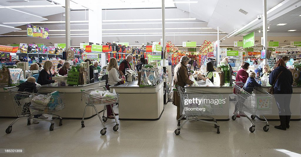 Customers load their purchases back into shopping carts after paying at check-out desks inside an Asda supermarket, the U.K. retail arm of Wal-Mart Stores Inc., in Watford, U.K., on Thursday, Oct. 17, 2013. U.K. retail sales rose more than economists forecast in September as an increase in furniture demand led a rebound from a slump the previous month. Photographer: Simon Dawson/Bloomberg via Getty Images