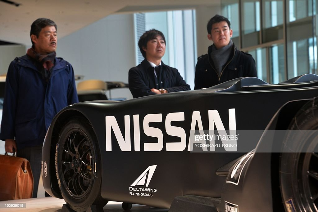 Customers look at a Deltawing racing car, powered by a Nissan Motor engine at Nissan's showroom in Yokohama, suburban Tokyo on February 8, 2013. Nissan said its net profit in the October-December quarter tumbled 34.6 percent from a year earlier, but the Japanese automaker kept its full-year profit forecast unchanged. AFP PHOTO / Yoshikazu TSUNO