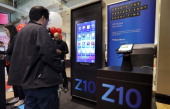 Customers look at a display of new BlackBerry Z10 at Rogers store at 333 BloorSt East in Toronto February 5 2013 Canadians who have clung to their...