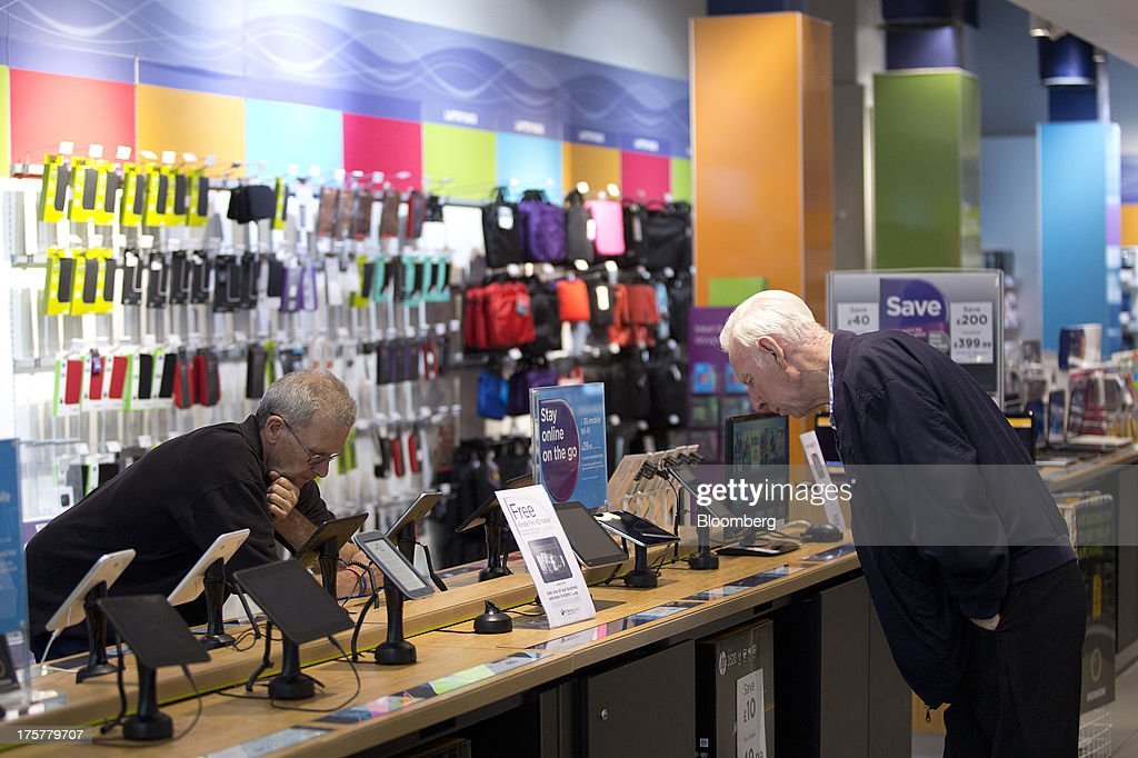 Customers look at a display of tablet devices inside a Currys and PC World 2 in 1 store, operated by Dixons Retail Plc, at the Westfield Stratford City retail complex in London, U.K., on Thursday, Aug. 8, 2013. U.K. consumer confidence rose to the highest in more than three years as Britons' optimism about the economic outlook improved. Photographer: Simon Dawson/Bloomberg via Getty Images