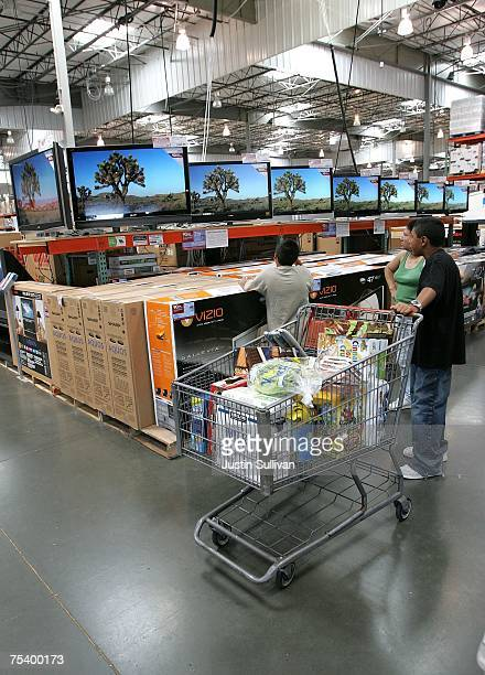 Customers look at a display of televisions at a Costco warehouse store July 13 2007 in Richmond California Costco Wholesale Corporation reported a...