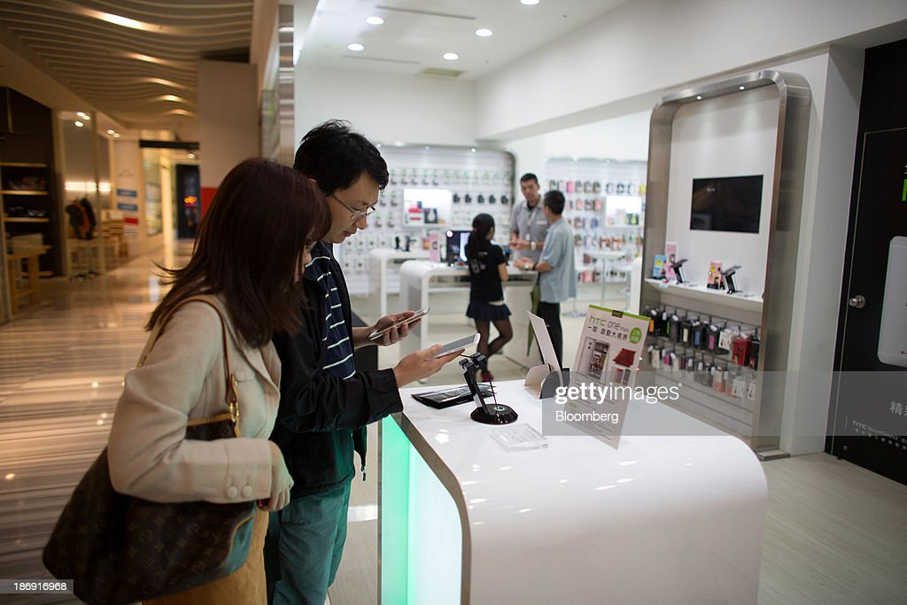 Customers look at a HTC Corp. One smartphone at one of the company's stores in Taipei, Taiwan, on Monday, Nov. 4, 2013. Taiwans five-year bonds gained for the first time in four days, lowering the yield from a three-week high, after a report showed inflation cooled. The local dollar strengthened. Photographer: Lam Yik Fei/Bloomberg via Getty Images
