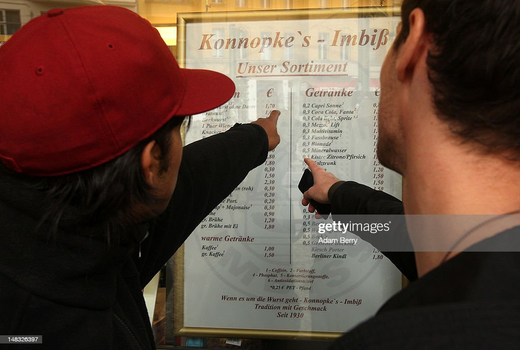 Customers look at a menu at Konnopke's currywurst stand on July 14, 2012 in Berlin, Germany. Currywurst, originally founded in post-war Berlin by Herta Heuwa, is Berlin's answer to fast food and is sold at specialized stands across the city and the rest of Germany. Currywurst is pork sausage, with or without casing, fried or deep-fried, that is typically smothered in curry powder and a ketchup-like sauce called curry sauce and served with french fries.