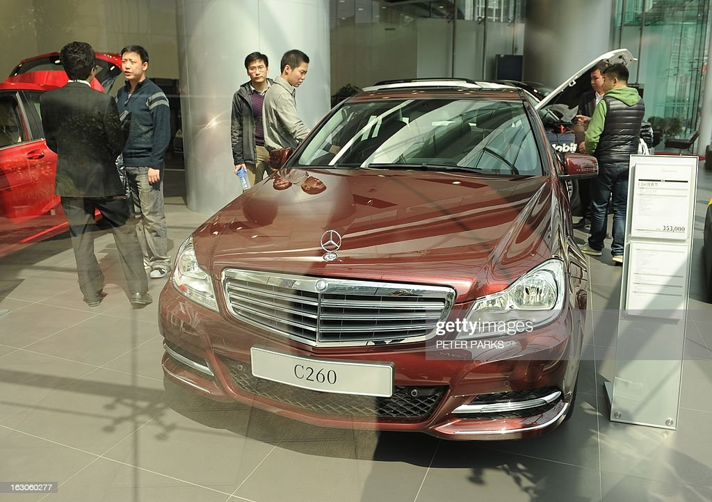 Customers look at a Mercedes Benz C260 in a showroom in Shanghai on March 4, 2013. China will overtake the US as the world's biggest luxury car market as early as 2016, as rising incomes and desire for status boost premium auto brands, a consultancy said. AFP PHOTO/Peter PARKS