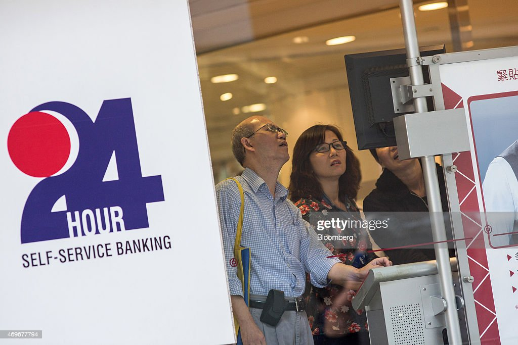 Customers look at a monitor displaying stock prices at a Bank of China Ltd branch in Hong Kong China on Tuesday April 14 2015 Chinese stocks trading...