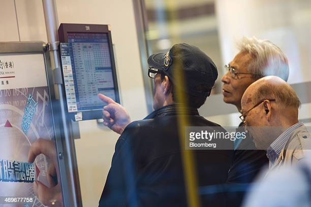 Customers look at a monitor displaying stock prices at a China Construction Bank Corp branch in Hong Kong China on Tuesday April 14 2015 Chinese...