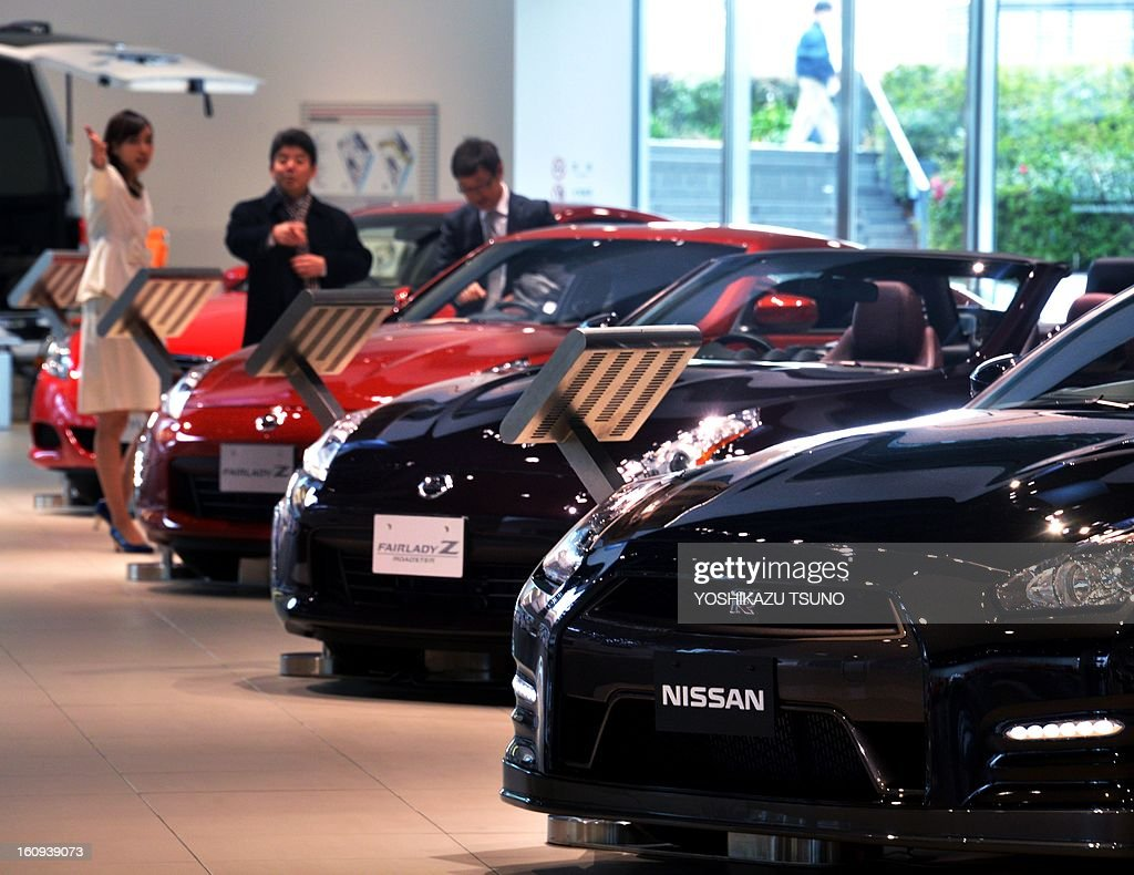 Customers look at a Nissan cars at Nissan's showroom in Yokohama, suburban Tokyo on February 8, 2013. Nissan said its net profit in the October-December quarter tumbled 34.6 percent from a year earlier, but the Japanese automaker kept its full-year profit forecast unchanged. AFP PHOTO / Yoshikazu TSUNO