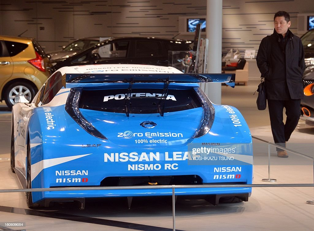 Customers look at a Nissan Leaf electric racing car at Nissan's showroom in Yokohama, suburban Tokyo on February 8, 2013. Nissan said its net profit in the October-December quarter tumbled 34.6 percent from a year earlier, but the Japanese automaker kept its full-year profit forecast unchanged. AFP PHOTO / Yoshikazu TSUNO