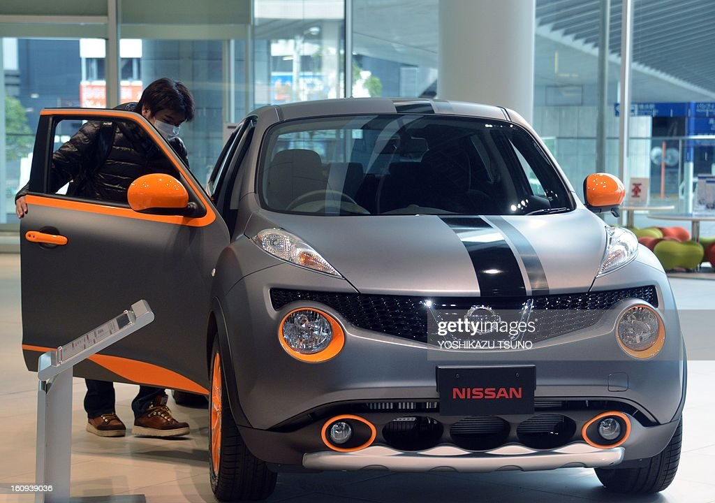 Customers look at a Nissan Motor's SUV 'Juke' at Nissan's showroom in Yokohama, suburban Tokyo on February 8, 2013. Nissan said its net profit in the October-December quarter tumbled 34.6 percent from a year earlier, but the Japanese automaker kept its full-year profit forecast unchanged. AFP PHOTO / Yoshikazu TSUNO