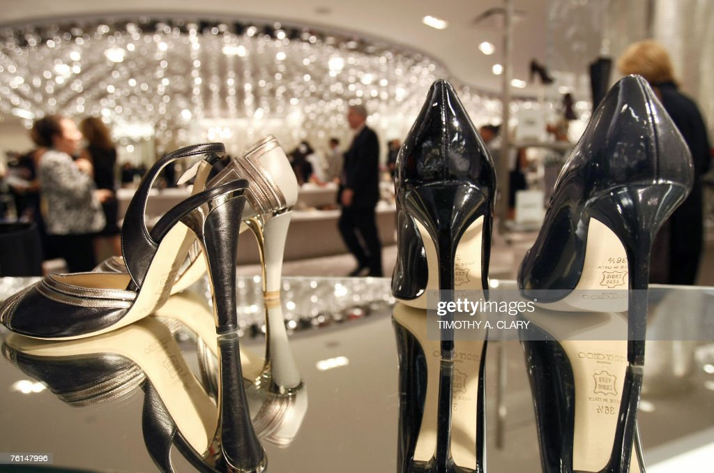 Customers look at a pair of Jimmy Choo heels as Saks Fifth Avenue unveils 17 August 2007 '10022SHOE' the new designer shoe floor that's so big it has...