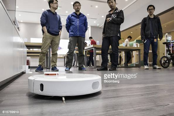 Customers look at a Xiaomi Corp Mi Robot Vacuum Cleaner operating inside one of the company's stores in Beijing China on Wednesday Oct 19 2016 Xiaomi...