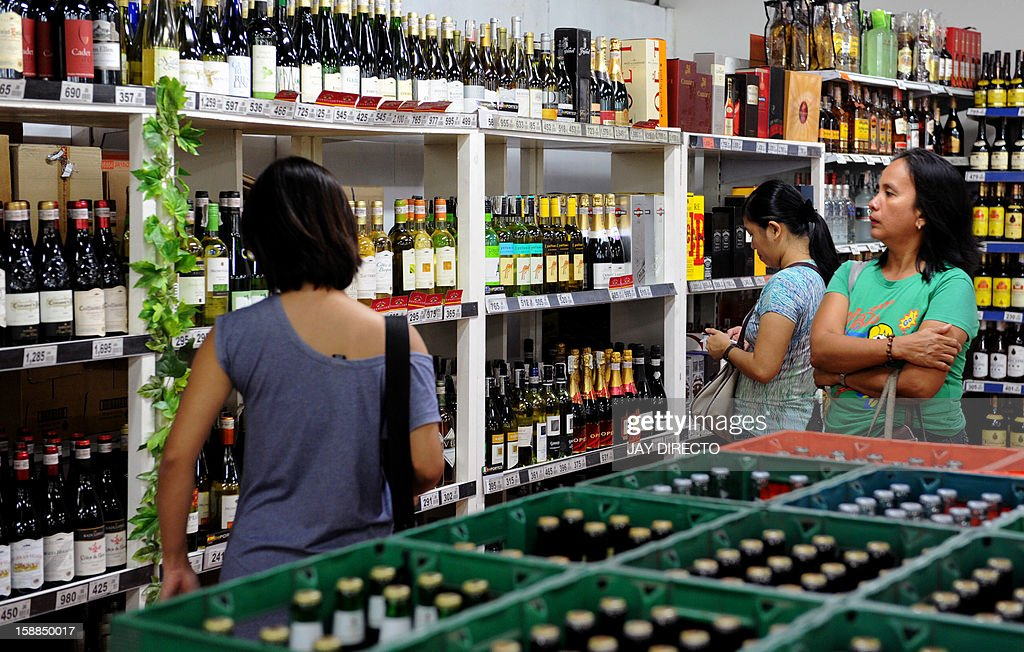 Customers look at alcoholic beverages on display at a supermarket in Manila on January 1, 2013. A 'sin tax' on cigarettes and alcohol dampened the New Year party spirit when it was introduced in the Philippines on January 1, as part of a government bid to boost finances.