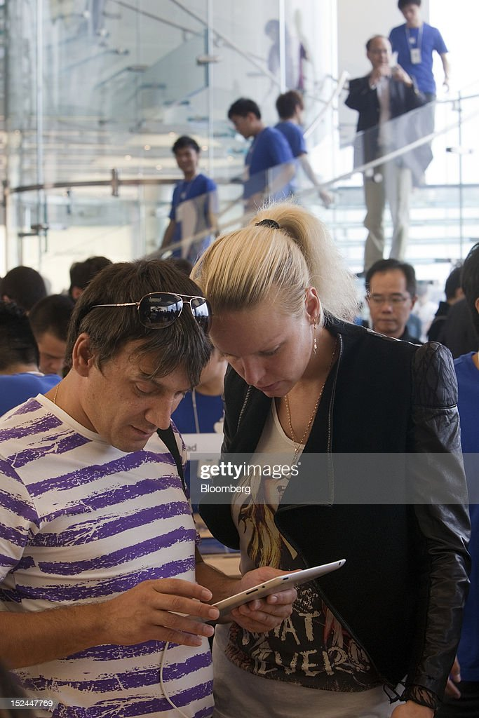 Customers look at an Apple Inc. iPad at the company's store in Hong Kong, China, on Friday, Sept. 21, 2012. Apple is poised for a record iPhone 5 debut and may not be able to keep up with demand as customers line up from Sydney to New York to pick up the latest model of its top-selling product. The device hits stores in eight countries today at 8 a.m. local time, giving customers in Australia the first chance to buy the device. Photographer: Daniel J. Groshong/Bloomberg via Getty Images