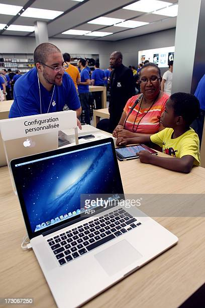 Customers look at an Apple's iPad Mini displayed near an Apple's MacBook Pro computer in a new Apple store on July 6 2013 in RosnysousBois near Paris...