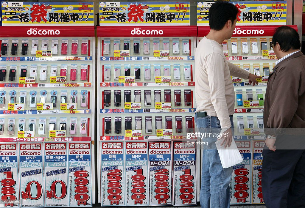 Customers look at an NTT DoCoMo Inc mobile phone display at an electronics store in Tokyo Japan on Friday Oct 30 2009 NTT DoCoMo Inc Japan's largest...