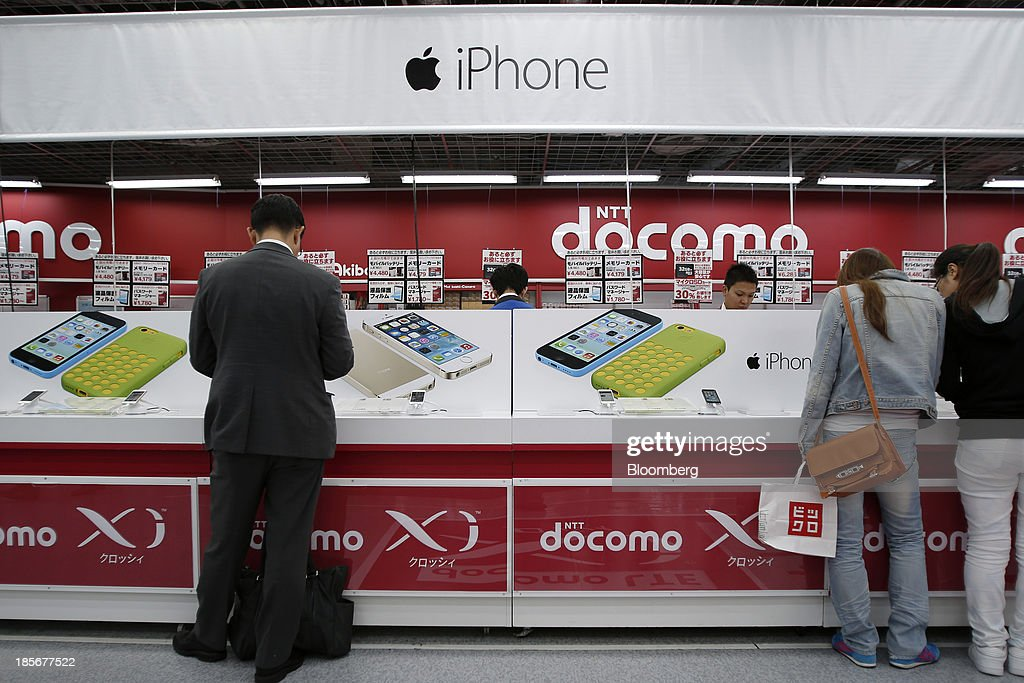 Customers look at Apple Inc. iPhone 5c and 5s smartphones for NTT Docomo Inc. on display at an electronics store in Tokyo, Japan, on Wednesday, Oct. 23, 2013. DoCoMo, Japan's largest mobile phone carrier, is scheduled to release earnings results on Oct. 25. Photographer: Kiyoshi Ota/Bloomberg via Getty Images