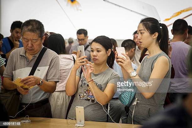 Customers look at Apple Inc's iPhone 6s and iPhone 6s Plus on display at the company's store during the sales launch at the IAPM shopping mall in...