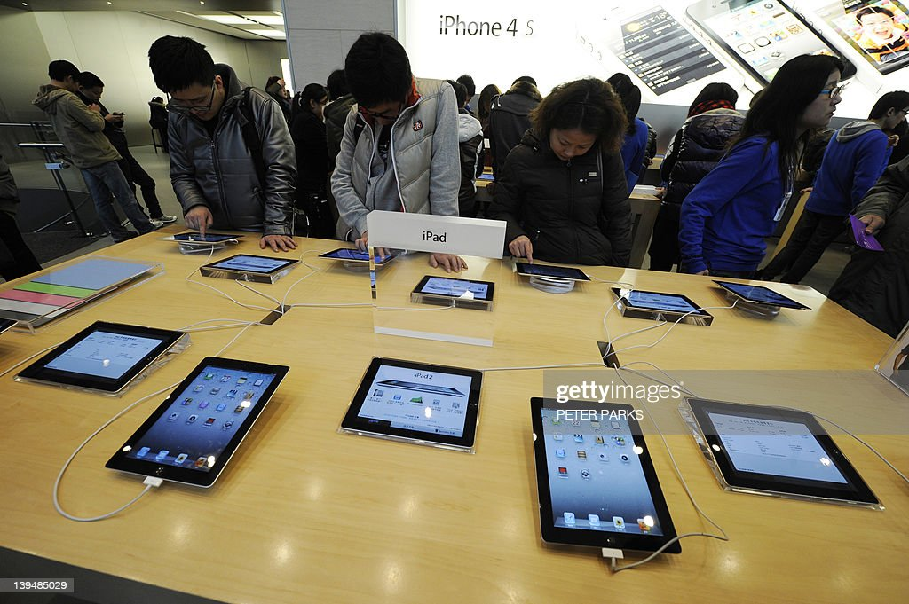 Customers look at Apple iPads at a store in Shanghai on February 22, 2012. A trademark dispute between Apple and a Chinese computer maker moved to Shanghai where the debt-laden plaintiff is seeking to stop the sale of the US giant's iconic iPad. AFP PHOTO/Peter PARKS