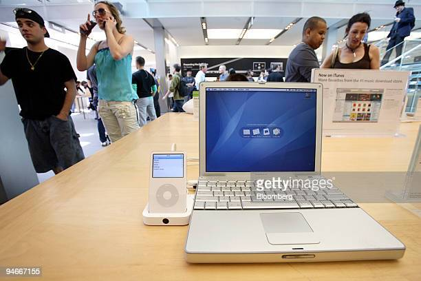 Customers look at Apple PowerBook G4 laptops and Apple iPods at the Apple Store in New York Tuesday April 18 2006
