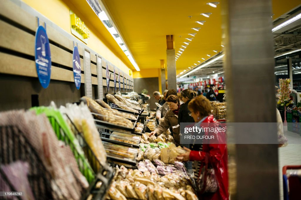 Customers look at breads at the bakery section of a Carrefour supermarket, on June 14, 2013 in Sainte-Geneviève-des-Bois, outside Paris. Installed in Sainte-Geneviève-des-Bois since fifty years, on June 15, 1963, this supermarket is the first of French giant retailer Carrefour group, but also the first in France. AFP PHOTO / FRED DUFOUR
