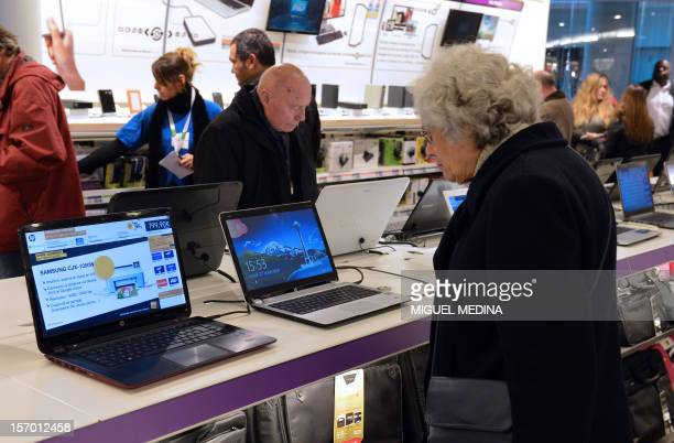 Customers look at computers displayed at a FNAC store on November 27 2012 in Paris AFP PHOTO MIGUEL MEDINA