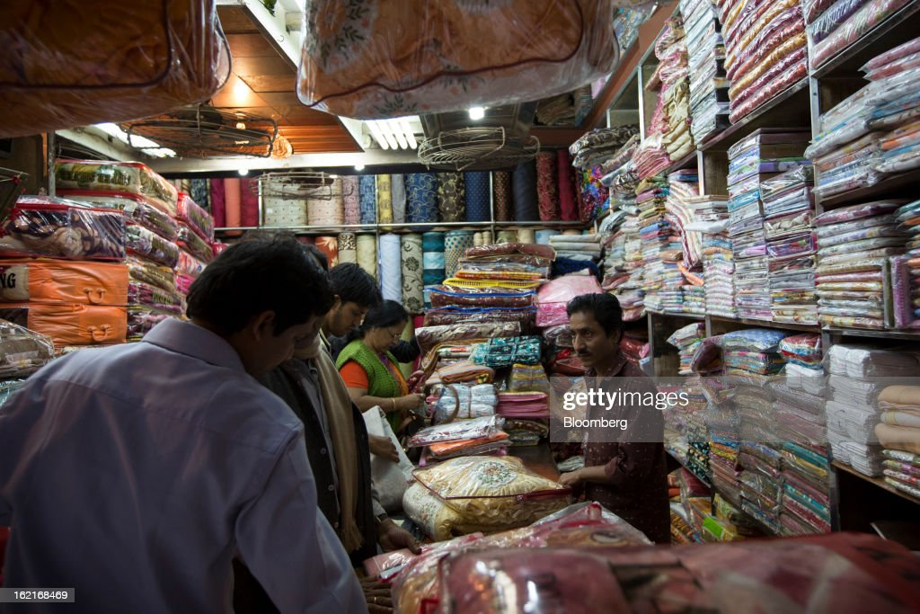 Customers look at fabric in a store in the Burrabazar area of Kolkata, India, on Tuesday, Feb. 19, 2013. India's slowest economic expansion in a decade is limiting profit growth at the biggest companies even as foreigners remain net buyers of the nation's stocks, according to Kotak Institutional Equities. Photographer: Brent Lewin/Bloomberg via Getty Images