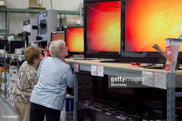 Customers look at flatpanel televisions inside a BJ's Wholesale Club Inc store in Falls Church Virginia US on Tuesday March 27 2012 The US Bureau of...