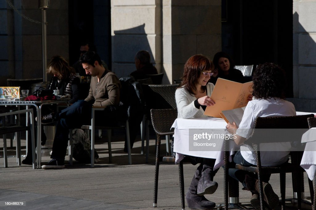 Customers look at food menus on the terrace of an outdoor cafe in Girona, Spain, on Thursday, Jan. 31, 2013. Spain's recession deepened more than economists forecast in the fourth quarter as the government's struggle to rein in the euro region's second-largest budget deficit weighed on domestic demand. Photographer: David Ramos/Bloomberg via Getty Images