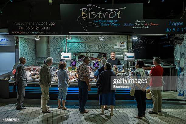 Customers look at fresh seafood on a fish stall at the Victor Hugo indoor market in Toulouse France on Tuesday Aug 12 2014 The euro traded 03 percent...
