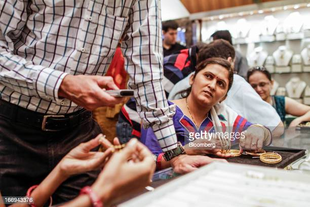 Customers look at gold jewelry at the Dwarkadas Chandumal Jewellers store in the Zaveri Bazaar area of Mumbai India on Thursday April 18 2013 A rush...