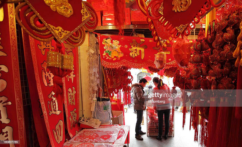 Customers look at items for Chinese New Year decorations at a store near Yu Garden in Shanghai, China, on Saturday, Feb. 2, 2013. China's services industries grew at the fastest pace since August as gains in retailing and construction aid government efforts to drive a recovery in the world's second-biggest economy. Photographer: Tomohiro Ohsumi/Bloomberg via Getty Images
