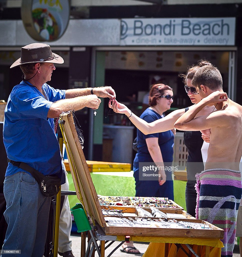 Customers look at jewelry at a market stall at Bondi Beach in Sydney, Australia, on Monday, Jan. 7, 2013. The Bureau of Statistics is scheduled to release retail sales data on Jan. 9. Photographer: Ian Waldie/Bloomberg via Getty Images