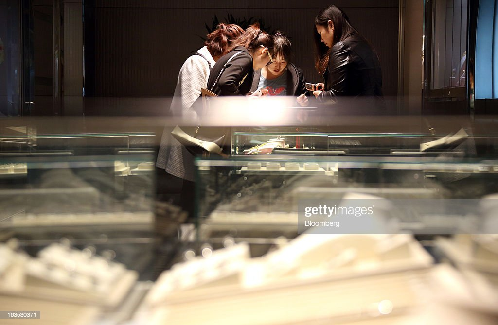 Customers look at jewelry displayed at the Chow Sang Sang Holdings International Ltd. jewelry store in the Sanlitun district of Beijing, China, on Monday, March 11, 2013. China's consumer prices climbed 3.2 percent from a year earlier, according to figures released March 9, exceeding January's 2 percent gain and the median estimate for a 3 percent increase in a Bloomberg survey of analysts. Photographer: Tomohiro Ohsumi/Bloomberg via Getty Images