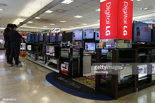 Customers look at LG Electronics Inc and Samsung Electronics Co televisions at a Hyundai I'Park Mall department store majorityowned by Hyundai...