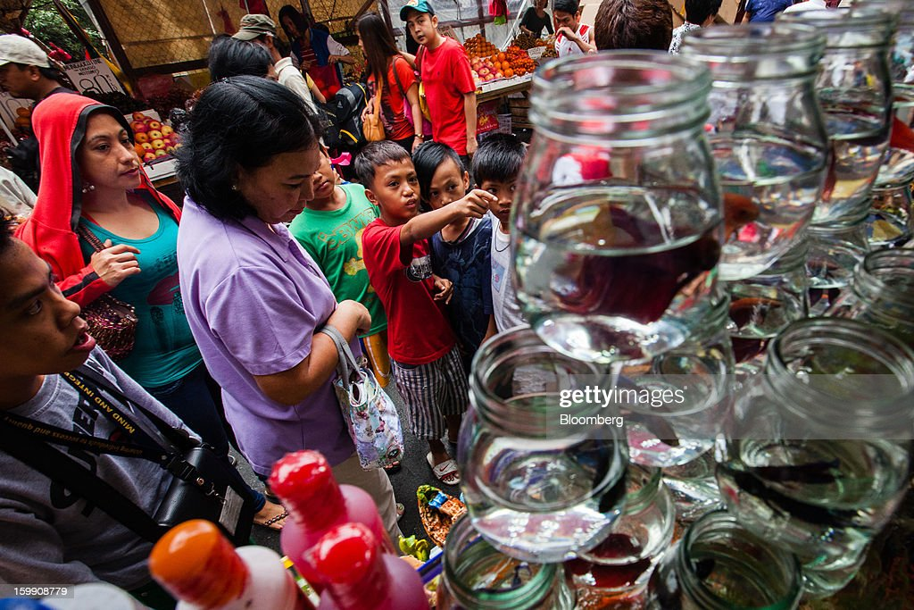 Customers look at pet fish for sale at the Divisoria market in Manila, the Philippines, on Tuesday, Jan. 22, 2013. Philippine government bonds advanced on speculation the central bank will hold its benchmark interest rate at a record low at a meeting tomorrow, supporting demand for the nation's debt. Photographer: Julian Abram Wainwright/Bloomberg via Getty Images