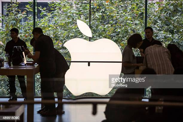 Customers look at products as an Apple Inc logo is illuminated at the store during the sales launch of the iPhone 6s and iPhone 6s Plus at the IAPM...
