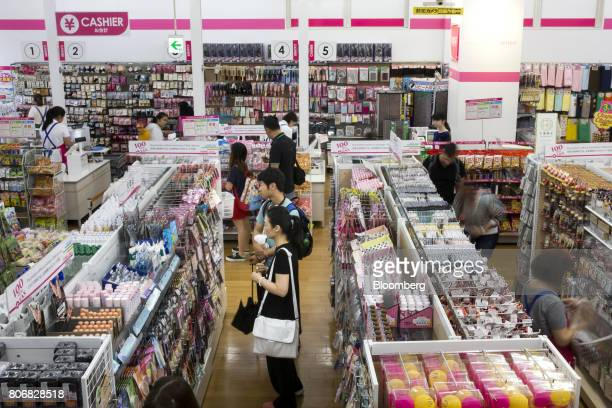 Customers look at products on display at a Daiso store operated by Daiso Sangyo Corp in the Harajuku area of Tokyo Japan on Friday June 30 2017...