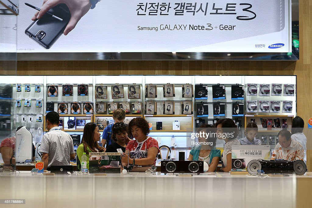 Customers look at Samsung Electronics Co. Galaxy smartphones at the company's d'light store in Seoul, South Korea, on Monday, July 7, 2014. Samsung Electronics is scheduled to report operating profit and sales figures on July 8. Photographer: SeongJoon Cho/Bloomberg via Getty Images