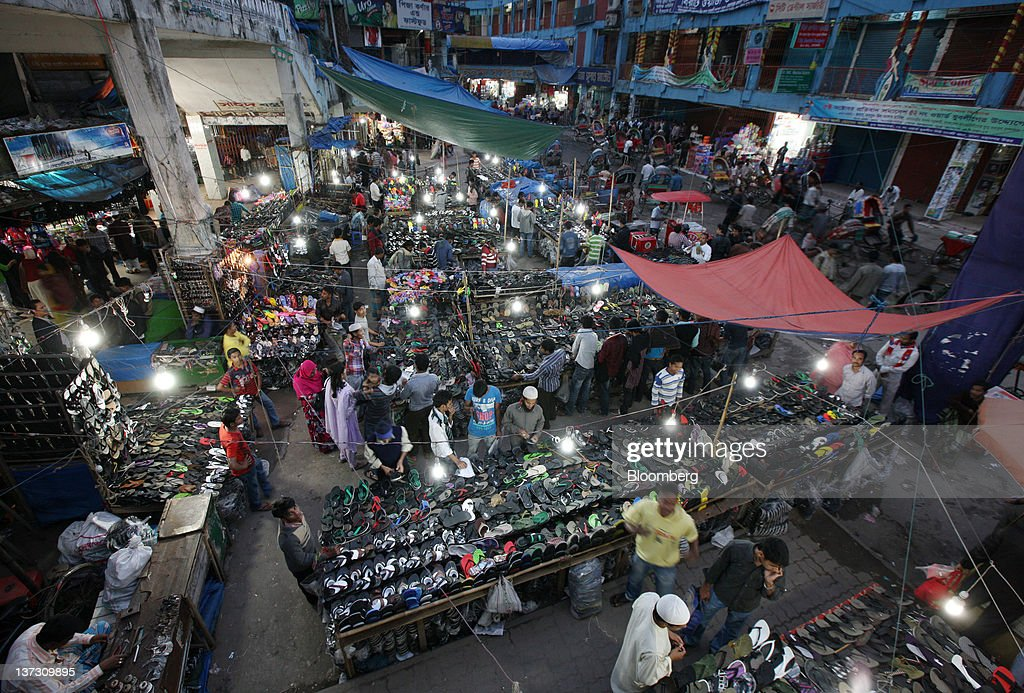 Customers look at sandals at a market in Dhaka, Bangladesh, on Tuesday, Jan. 10, 2012. Bangladesh's central bank this month raised interest rates for the second time in four months to curb inflation that has exceeded 9 percent since the start of 2011. Photographer: Tomohiro Ohsumi/Bloomberg via Getty Images