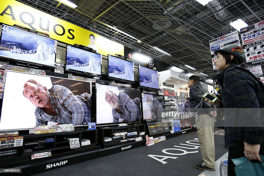 Customers look at Sharp Corp. Aquos televisions displayed at an electronics store in Tokyo, Japan, on Friday, Feb. 1, 2013. Sharp Corp., the Japanese TV-maker that has warned about its ability to survive, posted a narrower loss helped by job cuts, asset sales and a weaker yen. Photographer: Kiyoshi Ota/Bloomberg via Getty Images