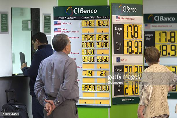 Customers look at the CI Bank currency exchange rates for the US dollar and the euro at the Benito Juarez International Airport in Mexico City Mexico...