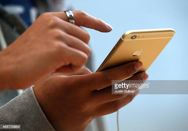 Customers look at the new iPhone 6 at an Apple Store on September 19 2014 in Palo Alto California Hundreds of people lined up to purchase the new...