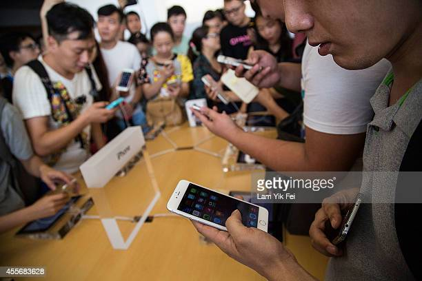 Customers look at the new iPhones on display at the launch of the new Apple iPhone 6 and iphone 6 plus at the Apple IFC store on September 19 2014 in...