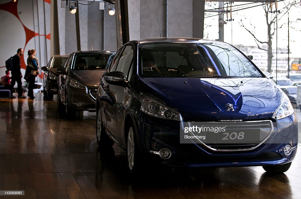 Customers look at the new Peugeot 208 automobiles, produced by PSA Peugeot Citroen SA, displayed at the company's headquarters in Paris, France, on Wednesday, March 28, 2012. PSA Peugeot Citroen SA, Europe's second-biggest carmaker, seeks leadership in the region's small-car segment with its new 208 model. Photographer: Balint Porneczi/Bloomberg via Getty Images